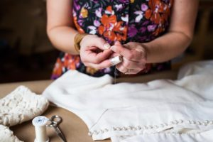 Brooks Ann hand sewing a wedding dress while using a thimble | Brooks Ann Camper Bridal Couture