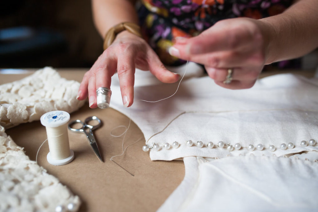 Brooks Ann hand sewing a wedding dress while using a thimble | Brooks Ann Camper Bridal Couture