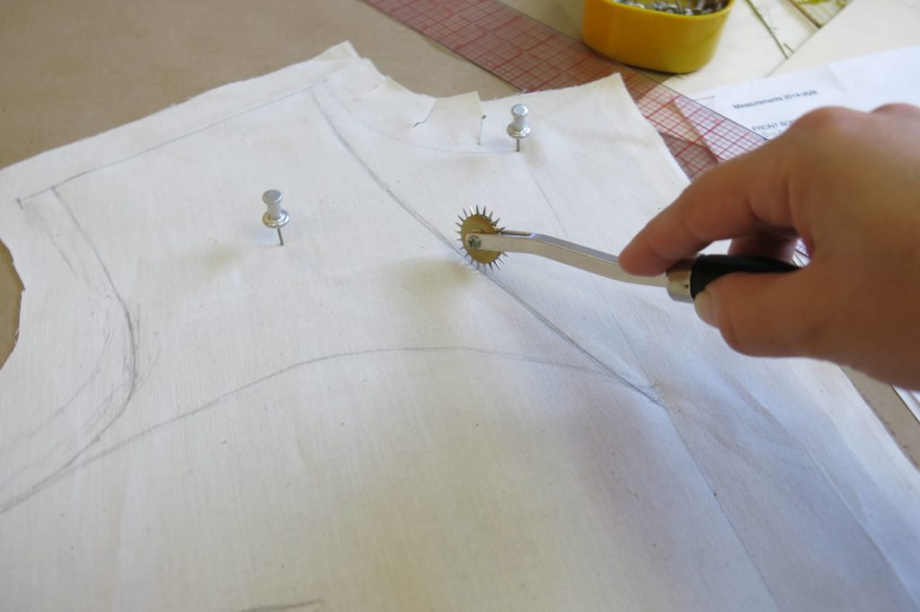 Using a spiky wheel to transfer the rough drape to the paper while Patternmaking for Cameron's custom wedding overdress by Brooks Ann Camper Bridal Couture